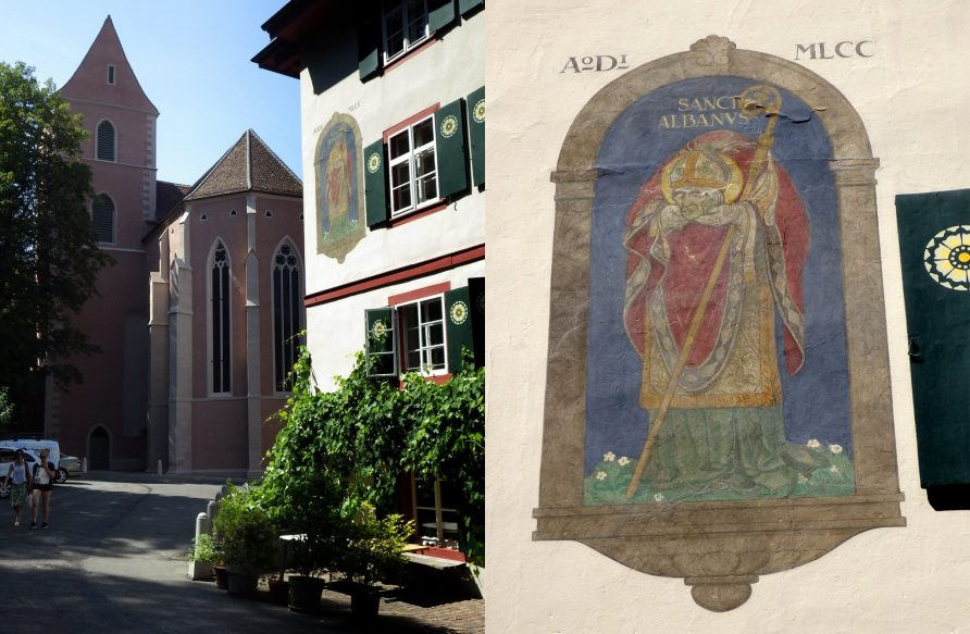 St Albankirche as it looks today with pink plaster. Right next to the church is a medieval building with St Alban himself depicted.